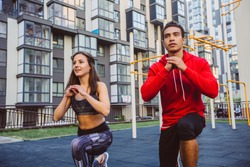 fitness, sport, lifestyle concept - smiling couple stretching outdoors. Mixed race man and latin hispanic woman athletes exercising lunges while having sports training on street sports ground.