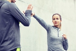 fitness, sport, martial arts, self-defense and people concept - woman with personal trainer working out strike outdoors