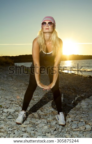 Fitness sport model doing exercises during outdoor work out on sunrise. Beautiful caucasian female training outside on seaside in the morning