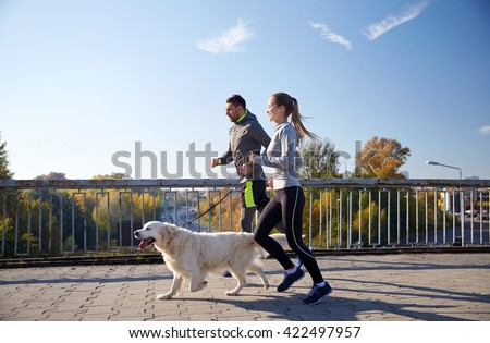 fitness, sport, people and jogging concept - happy couple with dog running outdoors #422497957