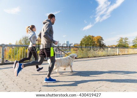fitness, sport, people and jogging concept - happy couple with dog running outdoors