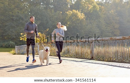 fitness, sport, people and lifestyle concept - happy couple with dog running outdoors #341561114