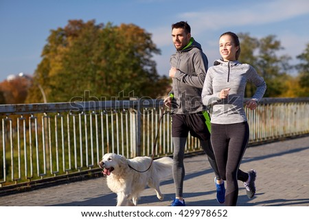 fitness, sport, people and lifestyle concept - happy couple with dog running outdoors #429978652