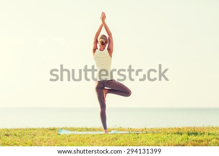 Stock Photo fitness, sport, people and lifestyle concept - woman making yoga exercises on mat outdoors from back