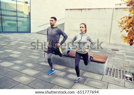 fitness, sport, people, exercising and lifestyle concept - couple doing lunge exercise on city street #651777694