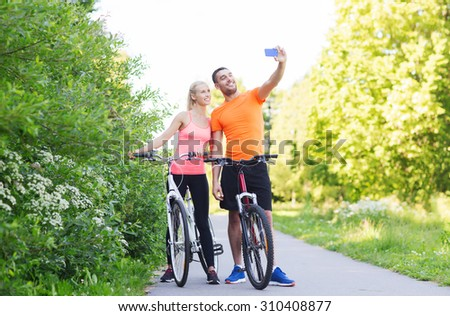 fitness, sport, people, technology and healthy lifestyle concept - happy couple with bicycle taking selfie by smartphone outdoors