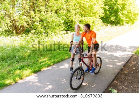 fitness, sport, summer, people and healthy lifestyle concept - happy couple with roller skates and bicycle riding and talking outdoors at park