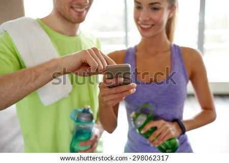 fitness, sport, technology and slimming concept - close up of smiling young woman and personal trainer with smartphone and water bottles in gym