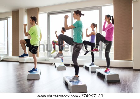 fitness, sport, training, aerobics and people concept - group of people working out with steppers in gym Photo stock ©