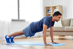fitness, sport, training and concept - indian man doing push ups at home
