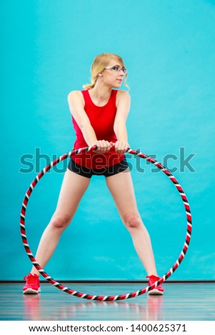 Fitness, sport, training and healthy lifestyle. Young woman in full length doing exercise with hula hoop, girl having fun playing game hula-hoop #1400625371