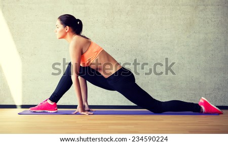 fitness, sport, training and lifestyle concept - smiling woman stretching leg on mat in gym
