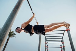 fitness, sport, training and lifestyle concept - young man exercising on bars outdoors - calisthenics
