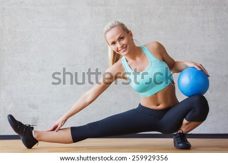 fitness, sport, training and people concept - smiling woman with exercise ball in gym