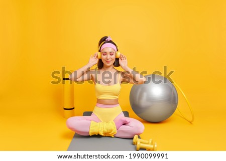 Fitness sport training concept. Sporty fit Asian woman sits crossed legs on mat enjoys listening music via headphones uses dumbbells fitball hula hoop has regular workout at home takes break