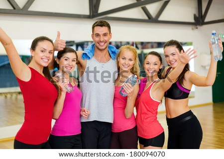 fitness, sport, training, gym and lifestyle concept - group of happy people in the gym with water bottles and towel showing thumbs up and waving hands