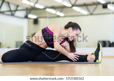 fitness, sport, training, gym and lifestyle concept - smiling teenage girl with earphones stretching on mat in the gym