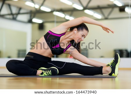fitness sport training gym and lifestyle concept stretching young woman with earphones in the gym