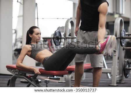 fitness, sport, training, teamwork and lifestyle concept - woman with personal trainer doing abdominal exercise in gym
