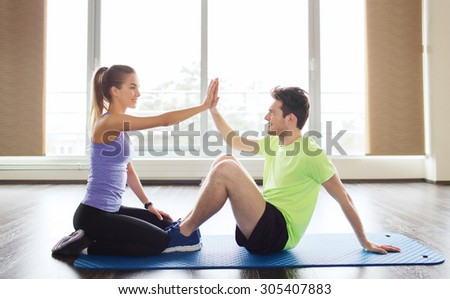 fitness, sport, training, teamwork and people concept - happy man with personal female trainer doing sit ups and high five gesture in gym