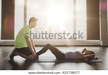 fitness, sport, training, teamwork and people concept - woman with personal trainer doing sit ups in gym