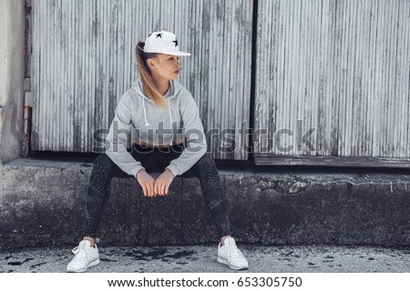 Fitness sporty girl wearing fashion sportswear over street wall, outdoor sports, urban style. Teen model in swag clothes posing outside.