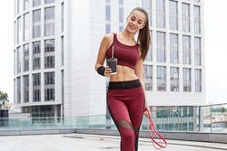 Fitness sporty woman during outdoor exercises workout. Beautiful fit Girl with  fitness elastic band and cup of coffee. Fitness model outdoors. Weight Loss. Healthy lifestyle. Sporty healthy female.