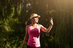 Fitness sporty woman runner in rural nature listening to music