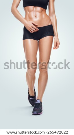 Fitness sporty woman walking in sports clothing. Close-up image of the legs and abs showing