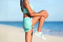 Fitness stretches woman runner stretching glute muscle with dynamic high knee pull stretch. Athlete getting ready to run doing leg muscles warm-up standing exercise on beach pre-workout. Body closeup.