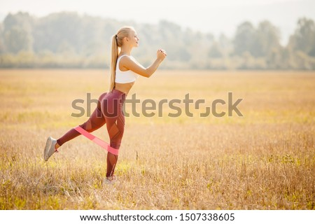 Fitness stretching rubber bands beautiful girl athlete blonde performs exercises outdoors in park.