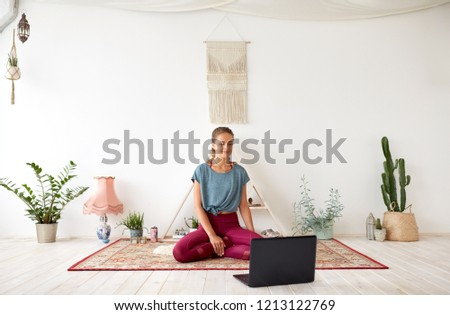 fitness, technology and healthy lifestyle concept - woman with laptop computer at yoga studio