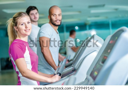 Fitness together on cross trainers. girl running on the CROSS TRAINERS and looking into the camera.