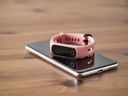 Fitness tracker on smartphone wooden tabletop. Pink female pedometer or wearable device on smartphone with infinity display, copy space