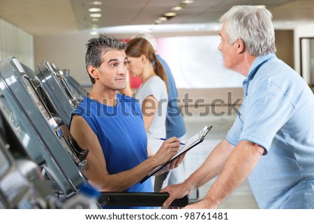 Fitness trainer coaching elderly man on treadmill in gym