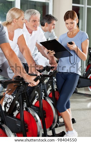 Fitness trainer coaching senior group in gym with stopwatch