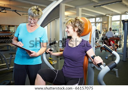Fitness trainer explaining rowing machine to woman in gym