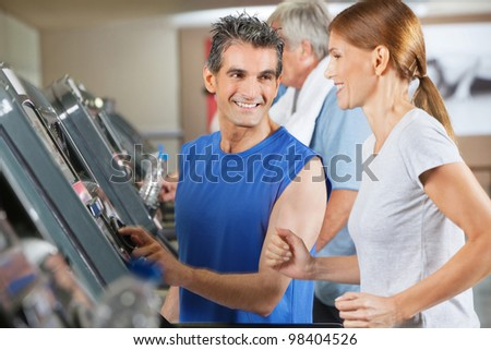 Fitness trainer explaining treadmill to jogging woman in gym