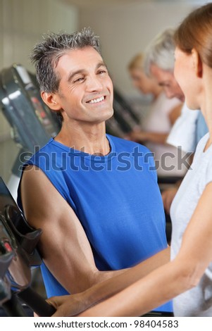 Fitness trainer flirting with woman on treadmill in gym