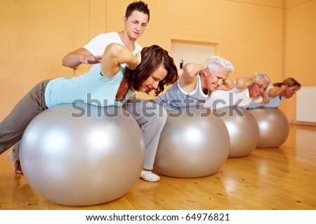 Fitness trainer in a gym teaching back exercises