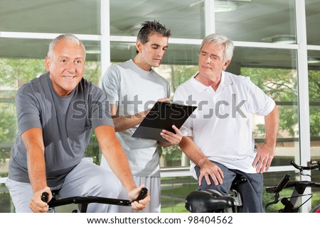 Fitness trainer with clipboard coaching happy senior people in gym