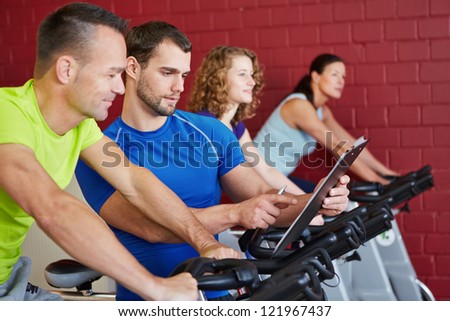 Fitness trainer with clipboard talking to a man on spinning bike
