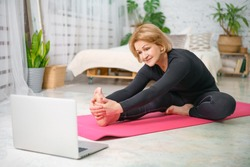 Fitness training online, senior woman at home with laptop.