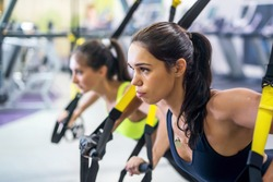 Fitness trx suspension straps training exercises women doing push-ups, working with own weith at gym