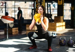 Fitness woman doing a weight training by lifting kettlebell. Muscular fitness woman, holds up a yellow kettlebell crossfit the gym. Fitness woman in the gym. Crossfit woman. Healthy lifestyle