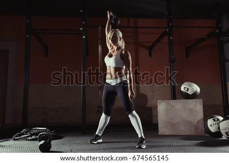 Fitness woman doing a weight training by lifting kettlebell. Muscular fitness woman, holds up a black kettlebell crossfit the gym. Fitness woman in the gym. Crossfit woman. Crossfit and fitness