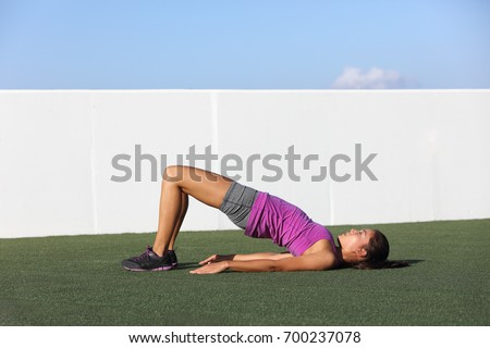 Fitness woman doing bodyweight glute floor bridge pose yoga exercise. Fit Asian woman exercising glutes muscles with floor bridge butt raise during summer in outdoor gym on grass.
