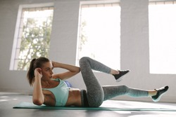 Fitness woman doing crunches exercise at gym. Sporty woman training over her abdominal core muscles for burning fat.