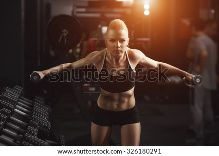 Fitness Woman doing exercises to warm up your muscles. Sporty woman in gym. Female holding barbells. Young woman, sport, workout - advertising concept. Blond woman in sport wear. Perfect fitness body.