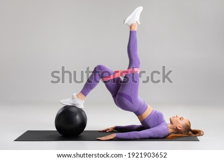 Fitness woman doing glute bridge exercise with resistance band on gray background. Athletic girl working out Photo stock ©